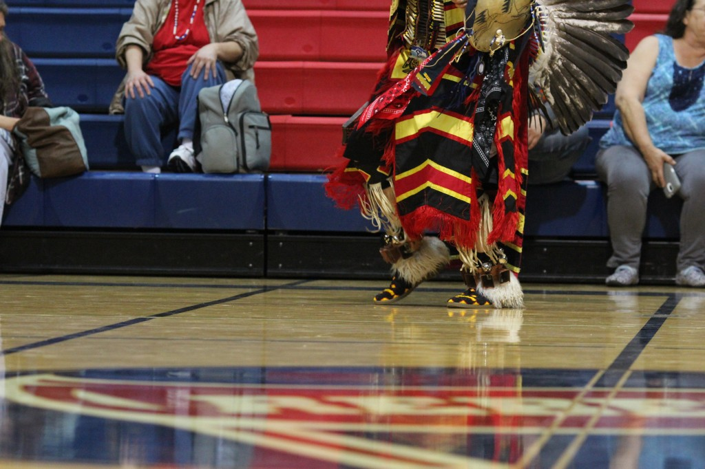 Man dressed in Native regalia walks at a Native American powwow